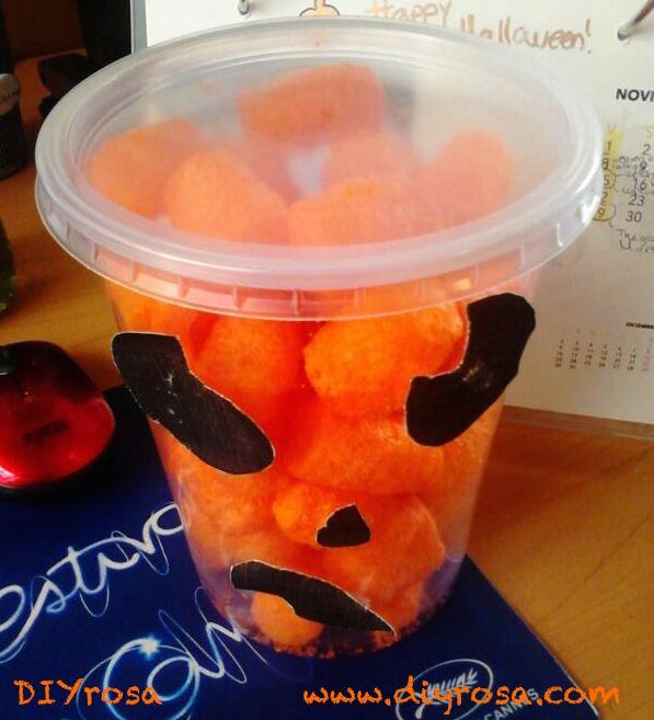 Cheetos en una envase transparente con ojos y boca de calabaza